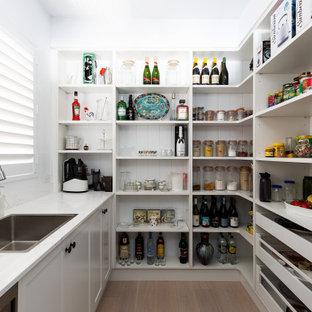 シドニーの中くらいのビーチスタイルのおしゃれなキッチン (ドロップインシンク、落し込みパネル扉のキャビネット、白いキャビネット、御影石カウンター、白いキッチンパネル、御影石のキッチンパネル、シルバーの調理設備、淡色無垢フローリング、ベージュの床、白いキッチンカウンター) の写真