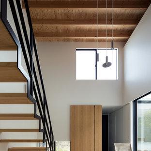 Diseño de salón abierto, minimalista, de tamaño medio, con suelo de contrachapado y televisor colgado en la pared