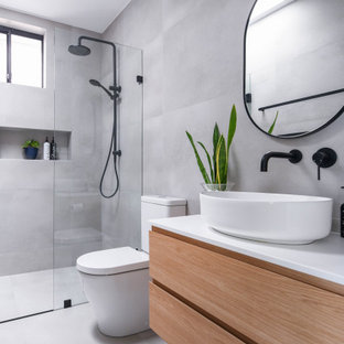 Mid-sized modern bathroom in Sydney with flat-panel cabinets, brown cabinets, gray tile, ceramic tile, ceramic floors, engineered quartz benchtops, grey floor, a hinged shower door, a niche, a single vanity, a floating vanity, a curbless shower, a two-piece toilet, a vessel sink and white benchtops.