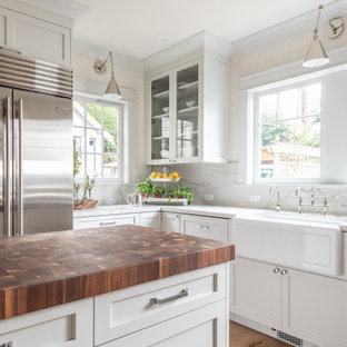 Geschlossene, Mittelgroße Klassische Küche in U-Form mit Landhausspüle, Schrankfronten mit vertiefter Füllung, weißen Schränken, Quarzit-Arbeitsplatte, Küchenrückwand in Weiß, Rückwand aus Stein, Küchengeräten aus Edelstahl, hellem Holzboden, Kücheninsel, braunem Boden, weißer Arbeitsplatte und Kassettendecke in Seattle