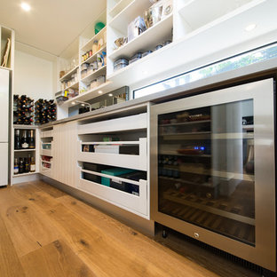 Huge beach style kitchen pantry designs - Inspiration for a huge beach style galley medium tone wood floor and brown floor kitchen pantry remodel in Melbourne with an undermount sink, open cabinets, white cabinets, quartz countertops, metallic backsplash, window backsplash, stainless steel appliances and no island