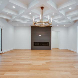 Großes, Offenes Klassisches Wohnzimmer mit weißer Wandfarbe, hellem Holzboden, Kamin, Kaminumrandung aus Holzdielen, gelbem Boden und Kassettendecke in Charlotte