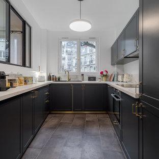 Idées déco pour une cuisine classique en U fermée et de taille moyenne avec un évier 1 bac, un placard avec porte à panneau encastré, des portes de placard noires, un plan de travail en stratifié, une crédence blanche, un sol en carrelage de céramique, un sol gris et un plan de travail blanc.