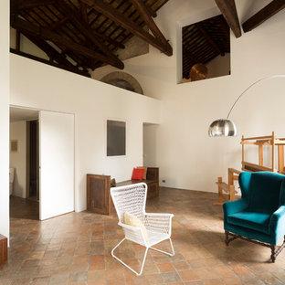 Esempio di un grande soggiorno country stile loft con pareti bianche, pavimento in terracotta, camino classico, cornice del camino in pietra, nessuna TV e pavimento rosa