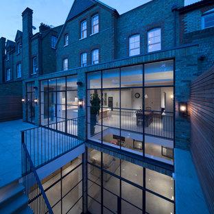 Ejemplo de fachada de casa bifamiliar marrón, industrial, extra grande, de tres plantas, con revestimiento de ladrillo, tejado a dos aguas y tejado de teja de barro