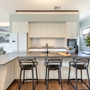 Photo of a contemporary galley open plan kitchen in Adelaide with an undermount sink, flat-panel cabinets, white cabinets, white splashback, mosaic tile splashback, white appliances, medium hardwood floors, with island, brown floor and grey benchtop.