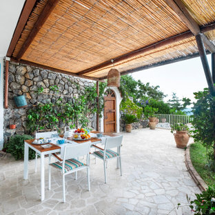 Ispirazione per un grande patio o portico mediterraneo davanti casa con pavimentazioni in pietra naturale e una pergola