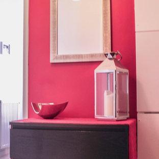 パリの小さいエクレクティックスタイルのおしゃれな玄関ラウンジ (ピンクの壁、塗装フローリング) の写真