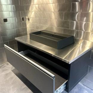 Стильный дизайн: туалет в современном стиле с плоскими фасадами, черными фасадами, унитазом-моноблоком, серой плиткой, металлической плиткой, серыми стенами, бетонным полом, настольной раковиной, столешницей из нержавеющей стали, серым полом, серой столешницей и подвесной тумбой - последний тренд