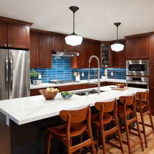 Eat-in kitchen - large transitional l-shaped light wood floor and yellow floor eat-in kitchen idea in San Francisco with a double-bowl sink, shaker cabinets, brown cabinets, blue backsplash, glass tile backsplash, stainless steel appliances, an island and white countertops
