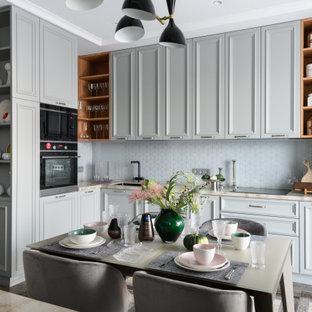 Стильный дизайн: угловая кухня-гостиная в стиле неоклассика (современная классика) с серыми фасадами, столешницей из акрилового камня, серым фартуком, черной техникой, полом из керамогранита, коричневым полом, бежевой столешницей, красивой плиткой, врезной раковиной, фасадами с утопленной филенкой и фартуком из плитки мозаики без острова - последний тренд