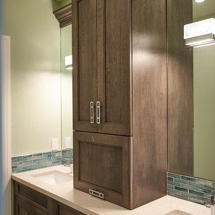 Diseño de cuarto de baño principal, de estilo americano, de tamaño medio, con armarios con paneles empotrados, puertas de armario marrones, baldosas y/o azulejos azules, baldosas y/o azulejos de vidrio laminado, paredes verdes, lavabo bajoencimera y encimera de cuarzo compacto