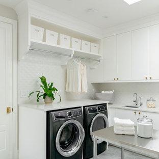 Idéer för att renovera ett stort vintage grå u-format grått grovkök, med en undermonterad diskho, släta luckor, vita skåp, bänkskiva i kvartsit, vitt stänkskydd, stänkskydd i keramik, grå väggar, vinylgolv, en tvättmaskin och torktumlare bredvid varandra och grått golv