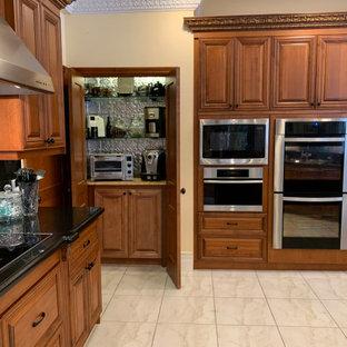 Idéer för ett mycket stort klassiskt svart skafferi, med en trippel diskho, luckor med upphöjd panel, skåp i mellenmörkt trä, granitbänkskiva, svart stänkskydd, stänkskydd i sten, rostfria vitvaror, klinkergolv i porslin, en köksö och beiget golv