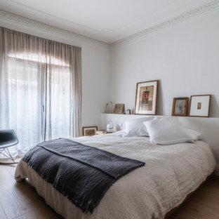 Ejemplo de dormitorio principal y casetón, actual, grande, con paredes blancas, suelo de madera clara y suelo marrón