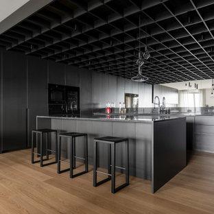 Esempio di una cucina moderna con lavello da incasso, ante lisce, ante gialle, top in granito, paraspruzzi nero, paraspruzzi in granito, elettrodomestici neri, parquet chiaro, top nero e soffitto a cassettoni