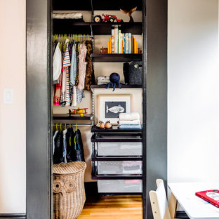 Inspiration for a small victorian gender-neutral built-in wardrobe in San Francisco with black cabinets, light hardwood floors and brown floor.