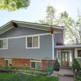 Amerikansk inredning av ett mellanstort blått hus, med två våningar, fiberplattor i betong, sadeltak och tak i mixade material