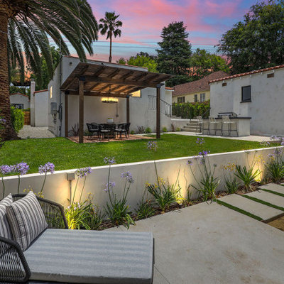 Inspiration for a mid-sized transitional backyard concrete paver and wood fence retaining wall landscape in Los Angeles with a fire pit.