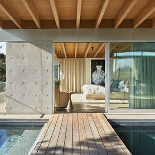 Inspiration for a huge modern backyard deck remodel in Seattle with a roof extension