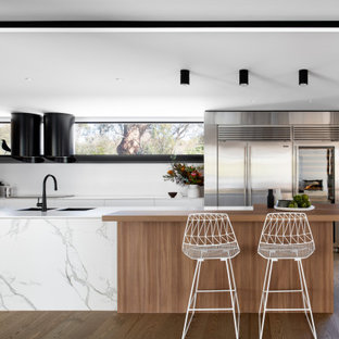 Design ideas for a large contemporary l-shaped kitchen pantry in Sydney with an undermount sink, flat-panel cabinets, solid surface benchtops, white splashback, black appliances, medium hardwood floors, with island and white benchtop.