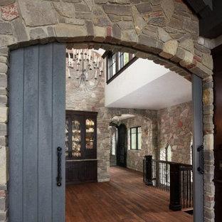 На фото: большое фойе в классическом стиле с коричневыми стенами, темным паркетным полом, двустворчатой входной дверью, серой входной дверью, коричневым полом и сводчатым потолком