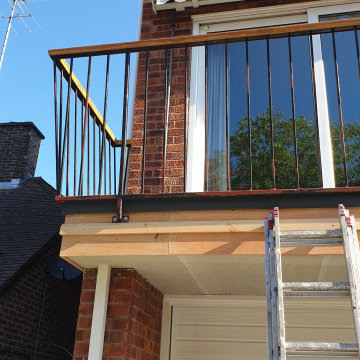 Front exterior - garage door, hand rail, and railing in West Wimbledon