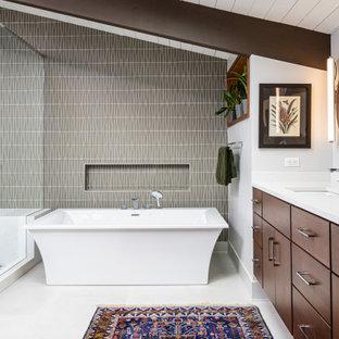 Idee per una stanza da bagno padronale moderna di medie dimensioni con ante lisce, ante in legno bruno, vasca freestanding, doccia ad angolo, WC monopezzo, piastrelle grigie, piastrelle di vetro, pareti grigie, pavimento in gres porcellanato, lavabo sottopiano, top in quarzo composito, pavimento bianco, porta doccia a battente, top bianco, due lavabi, mobile bagno sospeso e travi a vista