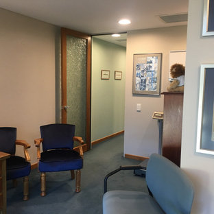 Стильный дизайн: большое рабочее место в современном стиле с коричневыми стенами, ковровым покрытием, отдельно стоящим рабочим столом и бирюзовым полом - последний тренд