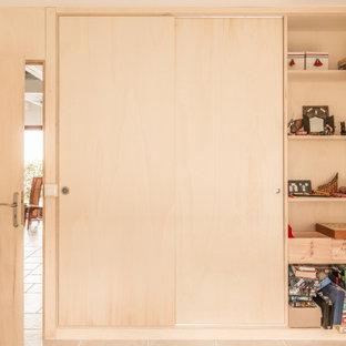 Ispirazione per una cameretta per bambini da 4 a 10 anni design di medie dimensioni con pareti multicolore, pavimento in travertino, pavimento beige, soffitto in carta da parati e pareti in legno