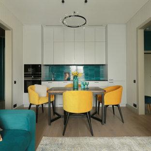 Идея дизайна: прямая кухня-гостиная среднего размера с врезной раковиной, плоскими фасадами, серыми фасадами, столешницей из кварцевого агломерата, зеленым фартуком, фартуком из керамической плитки, черной техникой, паркетным полом среднего тона, коричневым полом, черной столешницей и красивой плиткой без острова