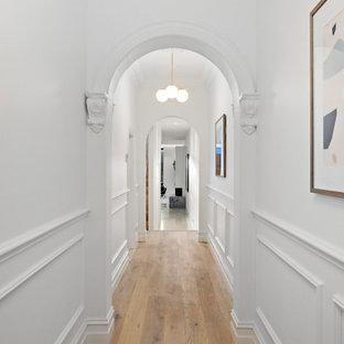Idéer för en mellanstor modern hall, med vita väggar och ljust trägolv