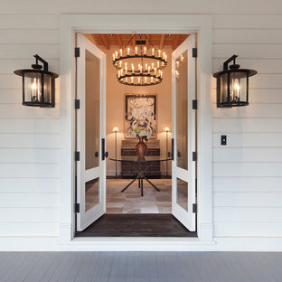 Example of a mid-sized eclectic dark wood floor entryway design in San Francisco with white walls and a white front door