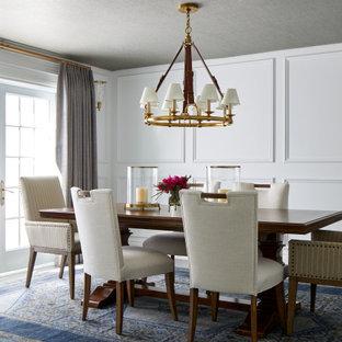 На фото: гостиная-столовая в стиле неоклассика (современная классика) с белыми стенами, серым полом, потолком с обоями и панелями на части стены с