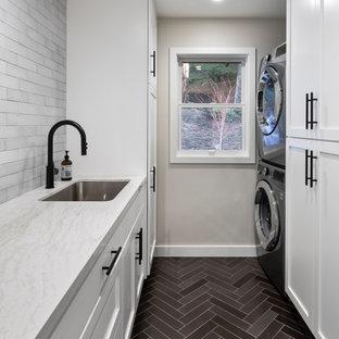 Foto di una sala lavanderia chic di medie dimensioni con lavello sottopiano, ante in stile shaker, ante bianche, top in quarzo composito, paraspruzzi grigio, paraspruzzi in mattoni, pavimento in gres porcellanato, lavatrice e asciugatrice a colonna, pavimento marrone e top bianco