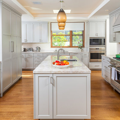 Inspiration for a mid-sized transitional u-shaped dark wood floor and brown floor enclosed kitchen remodel in Los Angeles with an undermount sink, shaker cabinets, gray cabinets, quartzite countertops, white backsplash, ceramic backsplash, stainless steel appliances, an island and gray countertops