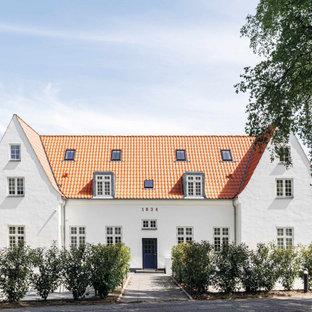 Стильный дизайн: четырехэтажный, белый частный загородный дом в скандинавском стиле с красной крышей - последний тренд