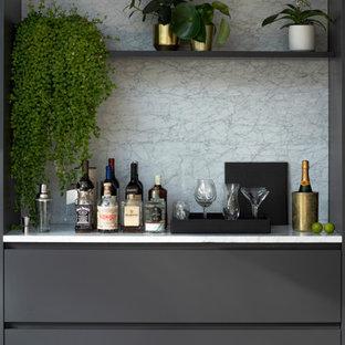 ロンドンの広いコンテンポラリースタイルのおしゃれなホームバー (グレーのキャビネット、大理石カウンター、淡色無垢フローリング) の写真