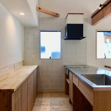 造り付けで作成したステンレス天板の造作キッチンと造作食器棚