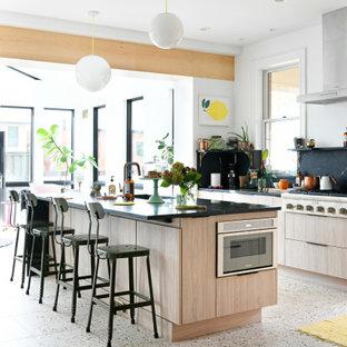 Diseño de cocina retro, abierta, con armarios con paneles lisos, puertas de armario de madera clara, encimera de mármol, salpicadero negro, salpicadero de mármol, electrodomésticos de acero inoxidable, suelo de terrazo y una isla