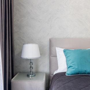 Immagine di una piccola camera degli ospiti chic con pareti grigie, pavimento in laminato, camino sospeso, cornice del camino in metallo, pavimento grigio e carta da parati