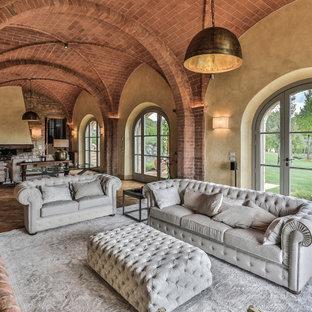 Esempio di un grande soggiorno mediterraneo con pareti gialle, pavimento in mattoni, pavimento rosso e soffitto a volta