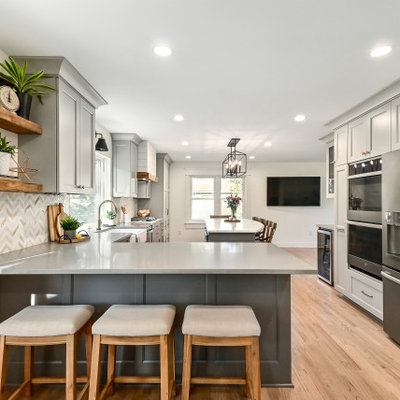 Huge farmhouse l-shaped medium tone wood floor and brown floor eat-in kitchen photo in Milwaukee with a farmhouse sink, shaker cabinets, gray cabinets, quartz countertops, white backsplash, marble backsplash, stainless steel appliances, an island and gray countertops