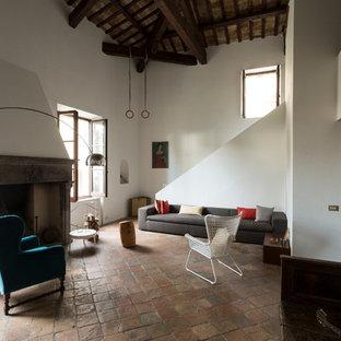 Cette image montre une grand salle de séjour mansardée ou avec mezzanine rustique avec un mur blanc, un sol en carreau de terre cuite, une cheminée standard, un manteau de cheminée en pierre, aucun téléviseur et un sol rose.