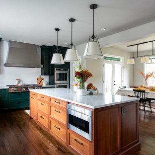 Mittelgroße Klassische Wohnküche in L-Form mit Landhausspüle, Schrankfronten im Shaker-Stil, grünen Schränken, Küchenrückwand in Weiß, Rückwand aus Metrofliesen, Elektrogeräten mit Frontblende, dunklem Holzboden, Kücheninsel, braunem Boden, grüner Arbeitsplatte und Quarzwerkstein-Arbeitsplatte in Seattle