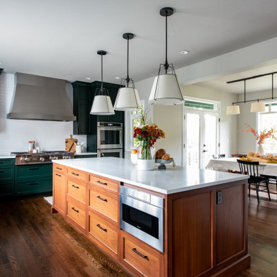 Eat-in kitchen - mid-sized transitional l-shaped dark wood floor and brown floor eat-in kitchen idea in Seattle with a farmhouse sink, shaker cabinets, green cabinets, white backsplash, subway tile backsplash, paneled appliances, an island, green countertops and quartz countertops