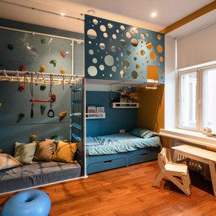 Esempio di una stanza dei giochi da 1 a 3 anni industriale di medie dimensioni con pareti bianche, pavimento in legno massello medio, soffitto ribassato e pareti in mattoni