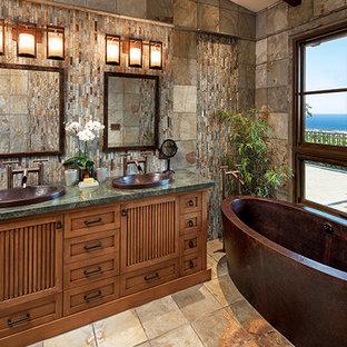 Ispirazione per una stanza da bagno padronale tropicale di medie dimensioni con ante con riquadro incassato, ante in legno scuro, vasca freestanding, lavabo da incasso, top in granito, pavimento marrone e top verde