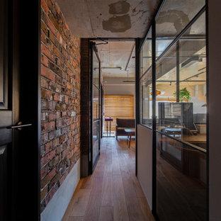 На фото: коридор в стиле лофт с разноцветными стенами, паркетным полом среднего тона, коричневым полом, балками на потолке и кирпичными стенами