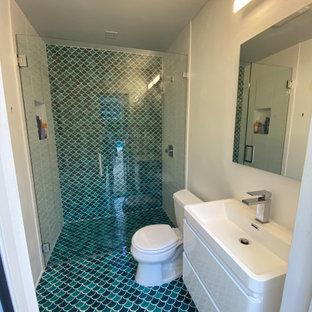 Exempel på ett litet klassiskt vit vitt badrum med dusch, med släta luckor, vita skåp, en kantlös dusch, en toalettstol med separat cisternkåpa, blå kakel, mosaik, vita väggar, mosaikgolv, ett integrerad handfat, blått golv och dusch med gångjärnsdörr